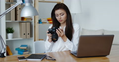 beautiful brunette photo editor in white shirt looking at a digital camera - stock footage