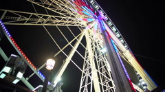 Merry night at amusement park, colorful illuminated giant Ferris wheel rotating Stock Footage