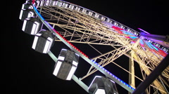 Huge Ferris wheel with illuminated passenger cars rotating fast, amusement ride Stock Footage