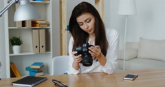 smiling brunette photo editor in white shirt looking at a digital camera - stock footage