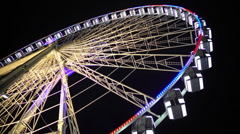 Huge observation wheel stops moving at night amusement park, entertainment Stock Footage