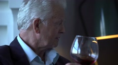 Elderly man drinking wine at home Stock Footage