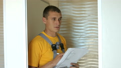 Young Man in Uniform Holds in Hand Blueprints. the Installation of Partitions Stock Footage