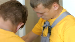 Two Young Workers Are Assembling Partition Walls in Toilet Cubicles. Mounting - stock footage