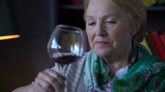 Elderly woman drinking wine at home Stock Footage