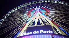 Colorful illuminated Rue de Paris observation wheel rotating under night sky Stock Footage