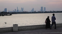 People walking on the Corniche. Sea coast in Bahrain. Manama skyline background Stock Footage