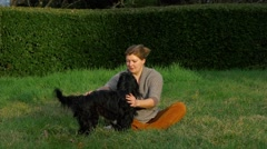 Young woman with her funny shaggy dog playing outdoors - stock footage