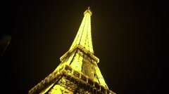 Vertical pan of Eiffel Tower, night in Paris, brightly illuminated construction Stock Footage