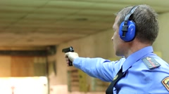 The officer fired a handgun at a shooting range Stock Footage