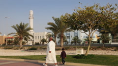 Muslim grandfather and his grandson walking in front the mosque - Bahrain Stock Footage