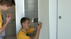 Workers Are Installing a Door Latch Lock on the White Door Stock Footage