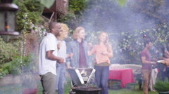 4K Happy mixed ethnicity group of friends chatting & having fun at bbq party Stock Footage