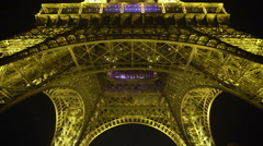 Crowded square at bottom of Eiffel Tower in Paris, popular tourist attraction Stock Footage