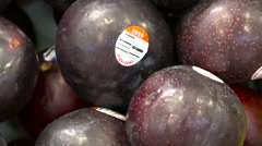 Assorted plums at market - fruit vegetable stand - stock footage