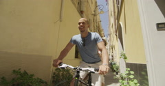 4K Attractive couple cycling in small Italian town and having fun.  Stock Footage