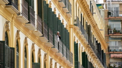 Elderly man smoking a pipe on a balcony of a house in the old town of Malaga - stock footage