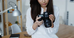 Attractive smiling brunette female photographer in white shirt checking an image Stock Footage