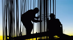 Behind a metal frame workers secure poles with wire to the base of a reinforc Stock Footage