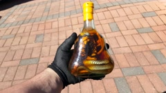 Man holding and touching a scorpion snake wine bottle in his hands - stock footage