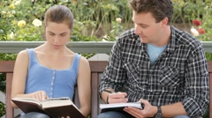 Students studying together with book writing notes for essay exam research paper - stock footage
