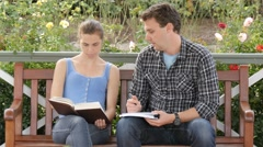 Student woman tutors man in study research taking written notes on campus - stock footage