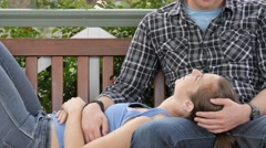 Young lovers in 20s show affection and romance cuddle on park bench in garden - stock footage