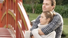 Attractive young couple in love cuddle and embrace outside in park - stock footage