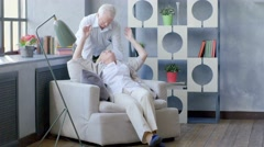 loving and happy elderly couple in a modern apartment. husband kisses his wife - stock footage