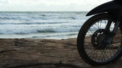 Silhouette of front wheel of motorcycle that is parked on the beach Stock Footage