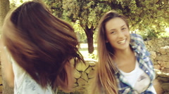 Cute female teenagers playing with camera in park hugging - stock footage