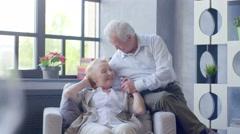 loving and happy elderly couple in a modern apartment. they talk, husband - stock footage