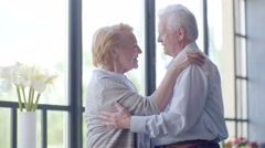 loving and happy elderly couple in a modern apartment. they talk, smile, hug and - stock footage