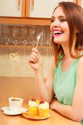 Woman with coffee eating cream cake. Gluttony. Stock Photos