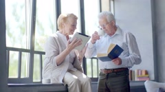 Happy lovely retired couple standing opposite each other with tablet and book - stock footage