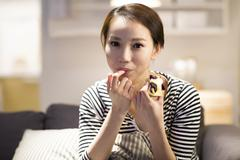 Happy young woman eating cake on sofa - stock photo