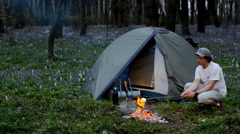 Tourist roast marshmallows over the campfire. Campground place, evening time - stock footage