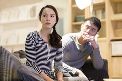 Young couple arguing on living room sofa Stock Photos