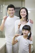 Happy young family brushing teeth - stock photo