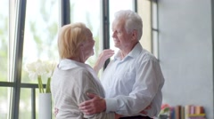 loving and happy elderly couple cuddling and talking in modern apartment - stock footage