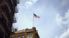 American flag on building waving in sky with fire escapes in NoHo in NYC Stock Footage