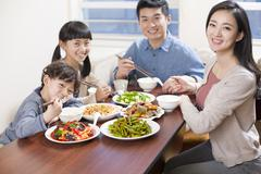 Happy young family having lunch Stock Photos