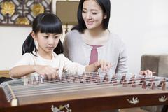 Mother teaching traditional musical instrument zither - stock photo