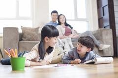 Happy siblings studying together at home Stock Photos