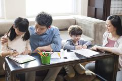 Young parents helping their children with homework Stock Photos
