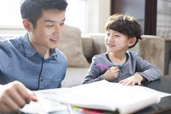 Young father helping son with homework - stock photo