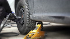 Mechanic changing a wheel of a modern car in a workshop Stock Footage