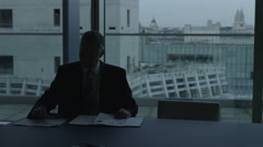 4KBusinessman alone with his thoughts in London office looks at view from window - stock footage