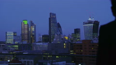4K Successful businessman alone with his thoughts looks out over view of London  - stock footage