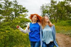 Girlfriends stroll arm in arm - stock photo